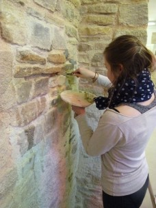 Lucie adds pointing mortar to a stone wall.